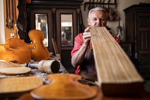 Senior timmerman ambachtsman houten plank kwaliteit controleren voor het werk