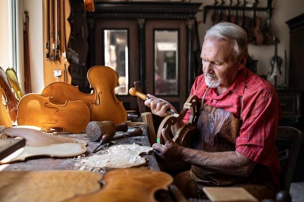 Senior timmerman ambachtsman houtsnijwerk in zijn ouderwetse werkplaats