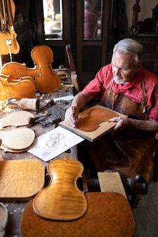 Senior timmerman ambachtsman viool muziekinstrument maken in de werkplaats van zijn ouderwetse timmerman