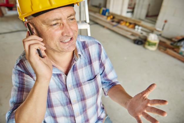 Senior timmerman met een telefoontje op de werkplaats