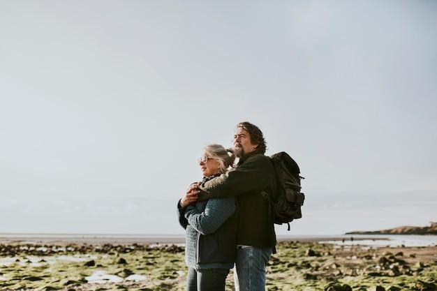 Senior toeristenpaar knuffelen op het strand