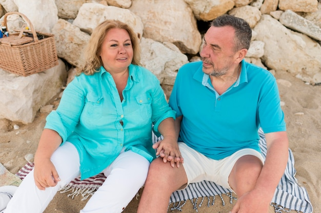 Senior toeristische paar op het strand hand in hand