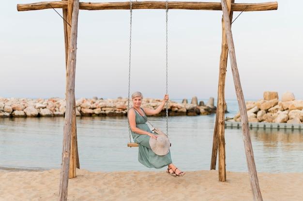 Senior toeristische vrouw in strand schommel
