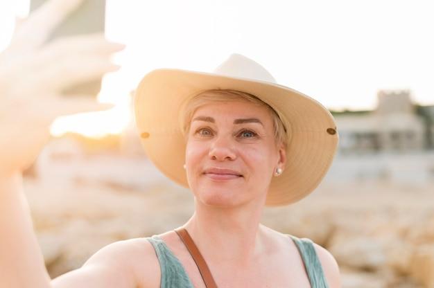 Senior toeristische vrouw smiley nemen selfie op het strand