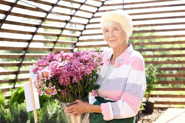 Senior tuinman poseren met bloemen
