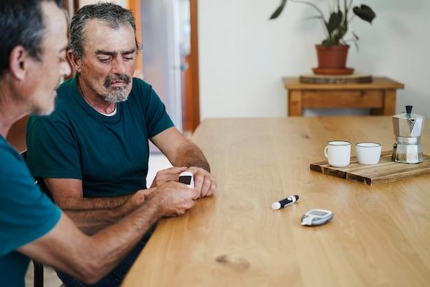 Senior twin man testen broer met vingertop pulsoximeter thuis - focus rechts gezicht