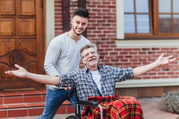 Senior vader in rolstoel en jonge zoon op een wandeling