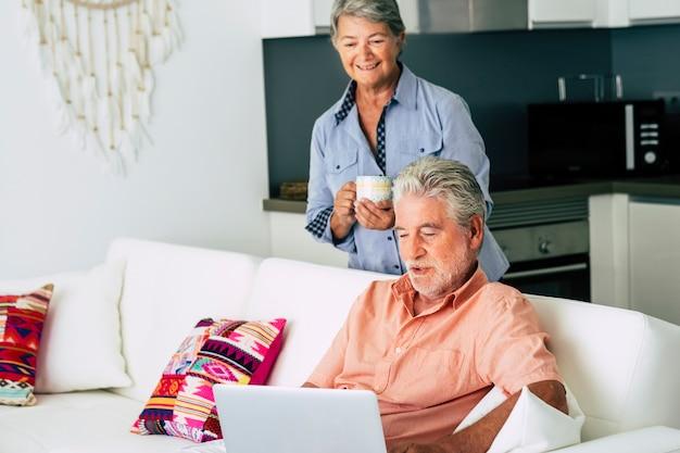 Senior volwassen blanke paar thuis met behulp van laptop moderne internetcomputer en samen plezier hebben in een getrouwde levensstijl