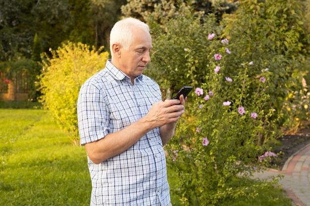 Senior volwassen man met behulp van mobiele telefoon in groen park, moderne technologieën