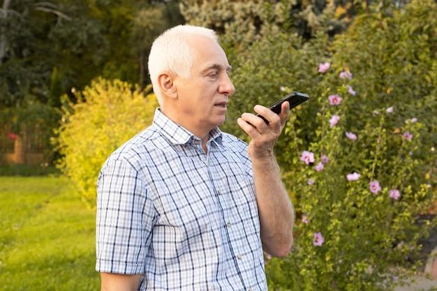 Senior volwassen oude man met behulp van mobiele telefoon met gesproken zoekopdrachten in groen park, moderne technologieën