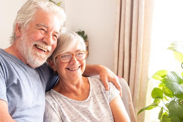 Senior volwassen paar zittend in de leunstoel. twee blanke mensen. grijs en wit haar. helder licht van raam. gelukkig en ontspannen pensioen. natuurlijke planten op de achtergrond
