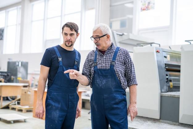Senior voorman in glazen met vinger wijzen en taak geven aan jonge afdrukken specialist in fabriek