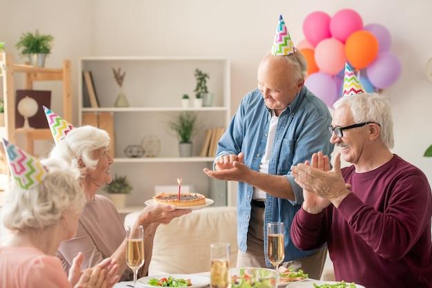 Senior vrienden handen klappen terwijl ze naar hun vriend met verjaardagstaart kijken door geserveerd tafel