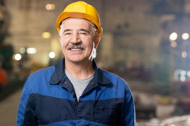 Senior vrolijke professionele poseren in grote industriële werkplaats