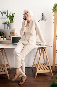 Senior vrolijke vrouw in elegant wit pak aanbrengen op bureau in kantoor en praten met vriend of familielid op smartphone
