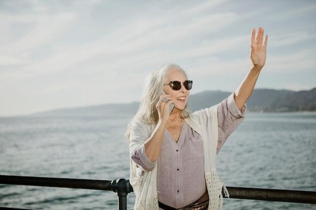 Senior vrouw aan de telefoon zwaaiend door de zee