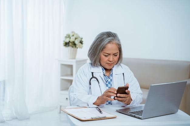 Senior vrouw arts met behulp van smartphone