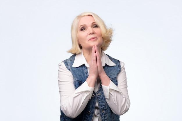 Senior vrouw bedelen en bidden met hoop uitdrukking op gezicht