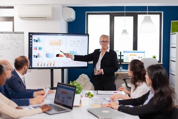 Senior vrouw bedrijfsleider brainstormen in vergaderruimte bedrijfspersoneel bespreekt nieuwe zakelijke toepassing met collega's die naar het scherm kijken