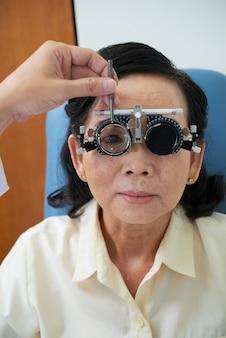 Senior vrouw bij oogheelkunde kliniek
