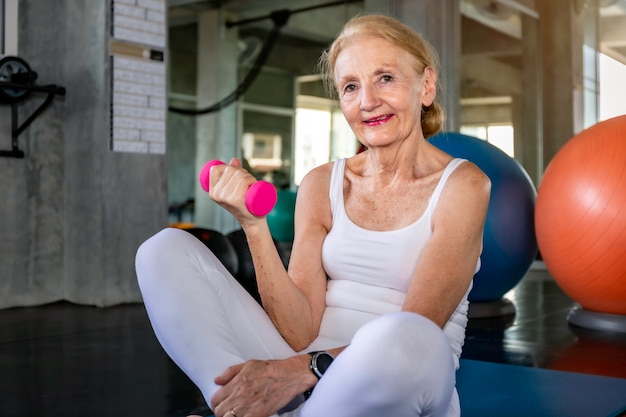 Senior vrouw blanke training arm met dumbell op fitness gym.