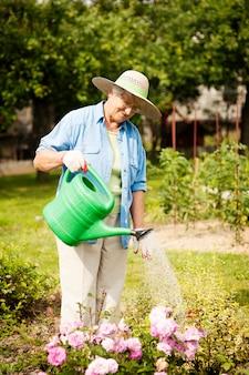 Senior vrouw bloemen water geven