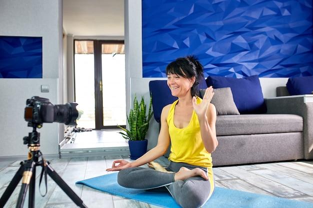 Senior vrouw blogger met slanke lichaamsvorm in sportkleding thuis yoga doen.