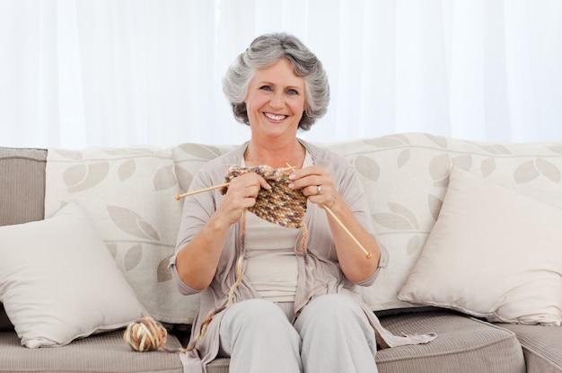 Senior vrouw breien op haar bank