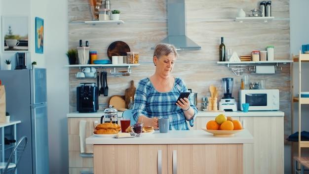 Senior vrouw browsen op mobiel in de keuken tijdens het ontbijt en glimlachen naar de camera. authentieke bejaarde die moderne smartphone-internettechnologie gebruikt. online communicatie verbonden met de wereld