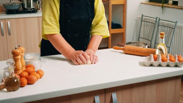 Senior vrouw chef kneedt het deeg op tafel in de moderne keuken. gepensioneerde bejaarde bakker met bonete die ingrediënten mengt met gezeefd tarwemeel dat knedt voor het bakken van traditionele cake en brood.