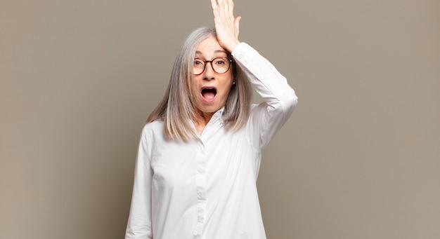 Senior vrouw die de handpalm naar het voorhoofd opheft, denkend oeps, na het maken van een domme fout of het herinneren, zich dom voelen