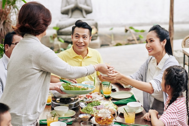Senior vrouw die diner serveert voor haar grote familie die samen het nieuwe maanjaar viert