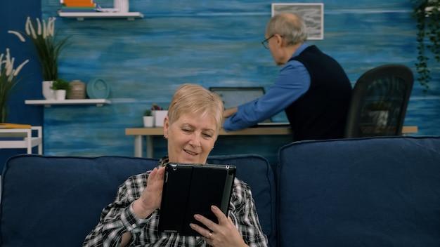 Senior vrouw die e-mails leest op digitale tablet die thuis op de bank zit