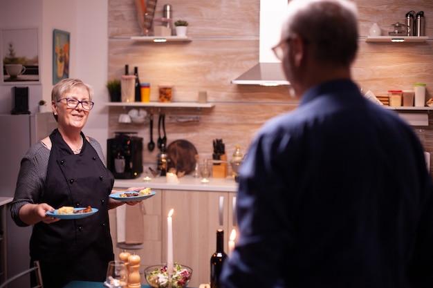 Senior vrouw die echtgenoot serveert met heerlijk eten voor hun relatieverjaardag. bejaard oud echtpaar praten, aan tafel zitten in de keuken, genieten van de maaltijd, vieren.