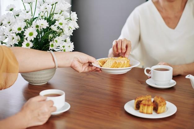 Senior vrouw die een bord met koekjes aanbiedt aan haar gast aan de keukentafel als ze thee drinken