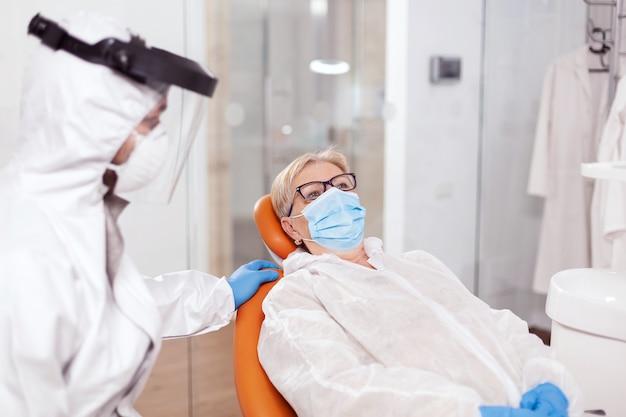 Senior vrouw die een hazmat-pak draagt in het stomatologiekantoor tijdens het coronavirus. oudere vrouw in beschermend uniform tijdens medisch onderzoek in tandheelkundige kliniek.