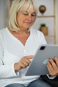 Senior vrouw die een online les volgt op haar tablet