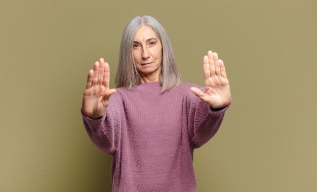 Senior vrouw die ernstig, ongelukkig, boos en ontevreden kijkt en de toegang verbiedt of stop zegt met beide open handpalmen
