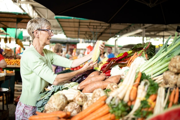 Senior vrouw die gezonde groenten kiest en koopt op de markt.