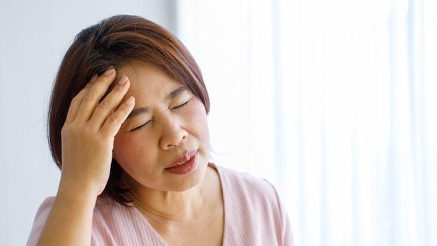 Senior vrouw die handen gebruikt om haar hoofd met pijn te vangen en vast te houden en lijdt aan een vervormd gezicht door hoofdpijn met cerebrovasculaire ziekte of een beroerte.