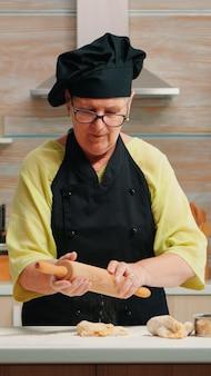 Senior vrouw die het deeg uitrolt en zelfgebakken brood bereidt. gelukkige bejaarde chef-kok met bonete die rauwe ingrediënten bereidt voor het bakken van traditionele pizzabestrooiing, zeven van bloem op tafel in de keuken.