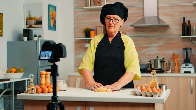 Senior vrouw die inhoud maakt voor culinaire blog die smakelijk brood bereidt. gepensioneerde blogger-chef-beïnvloeder die internettechnologie gebruikt om te communiceren, bloggen op sociale media met digitale apparatuur