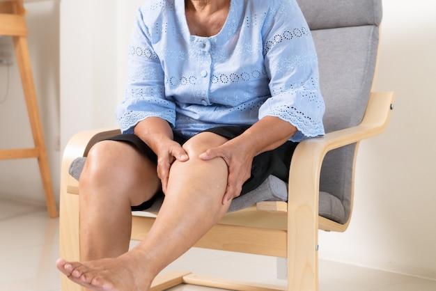 Senior vrouw die lijdt aan kniepijn thuis, gezondheidsprobleem concept