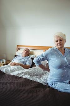 Senior vrouw die lijdt aan rugpijn zittend op bed