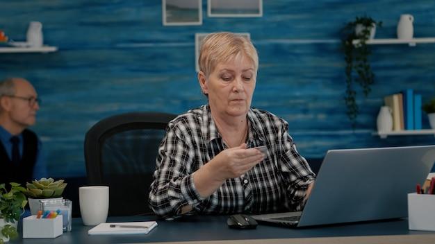 Senior vrouw die online betaalt met creditcard op laptop die thuis werkt, gepensioneerde oude persoon