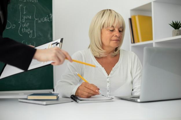 Senior vrouw die oplet in de klas
