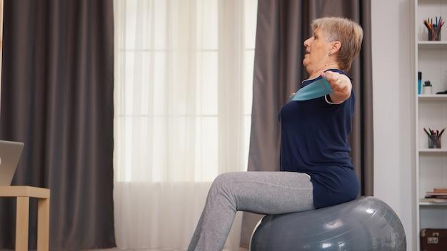 Senior vrouw die sport doet op stabiliteitsbal met weerstandsband gepensioneerde oude vrouw die fitness uitrekt en een gezonde levensstijl leeft bij pensionering, training thuis oefening