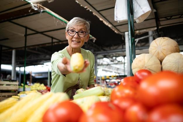 Senior vrouw die suikermaïs en fruit koopt op de markt en een zak vol gezond voedsel vasthoudt
