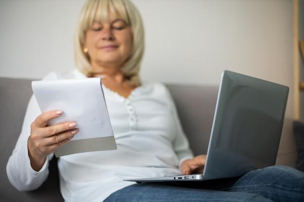 Senior vrouw die thuis een online les volgt op haar laptop