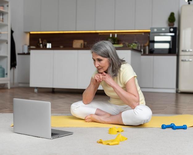 Senior vrouw die thuis fitnessles op laptop volgt